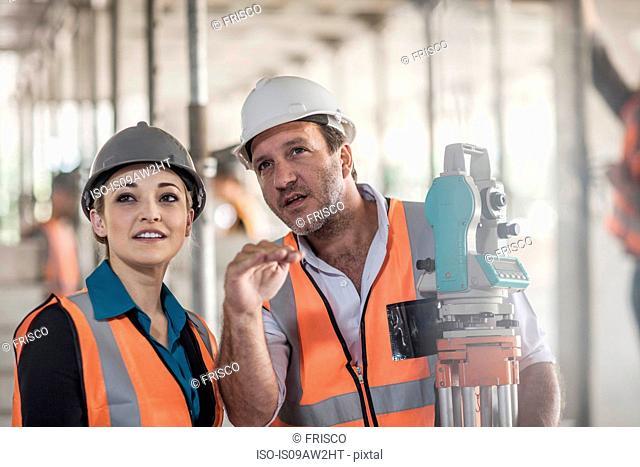Surveyor explaining to female builder on construction site