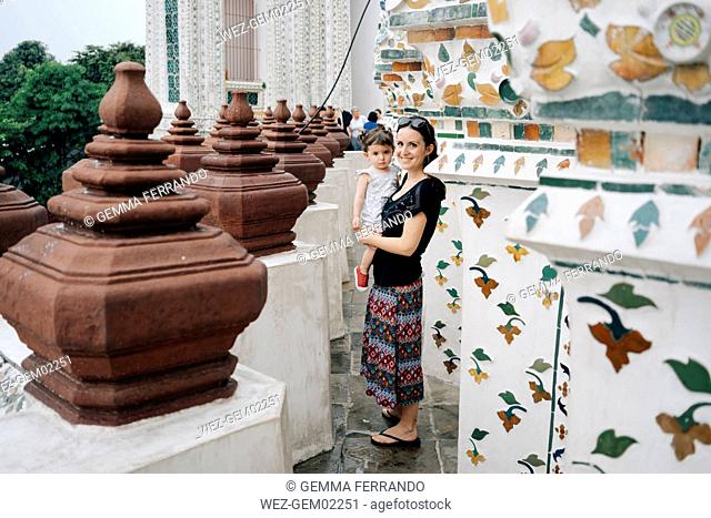 Thailand, Bangkok, Wat Arun, Portrait of smiling mother and daughter visiting the Buddhist temple