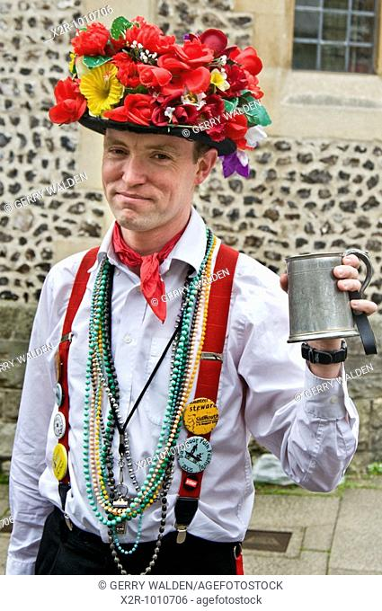 Morris dancer with floral hat and tankard of beer taking part in the Winchester Spring Festival in England