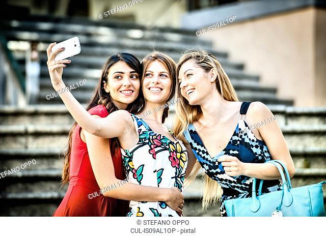 Three fashionable young women taking selfie on stairway, Cagliari, Sardinia, Italy