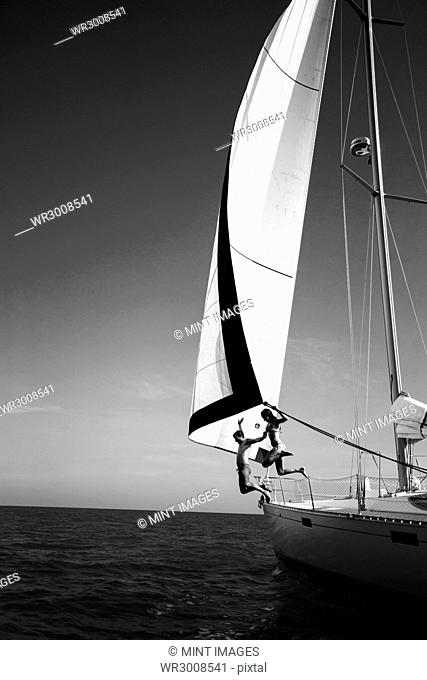 Two people jumping from a yacht into the ocean