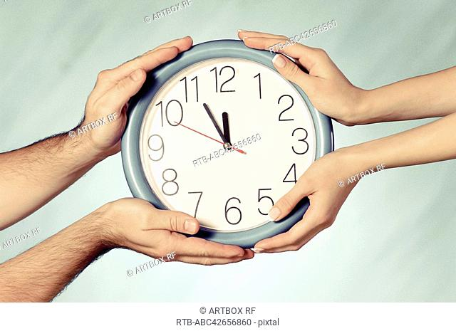 Close-up of a man and a woman's hands holding a wall clock