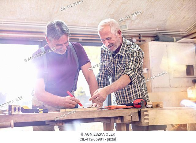 Male carpenters marking and measuring wood in workshop