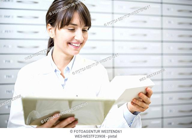 Smiling pharmacist with tablet and tablet package in pharmacy