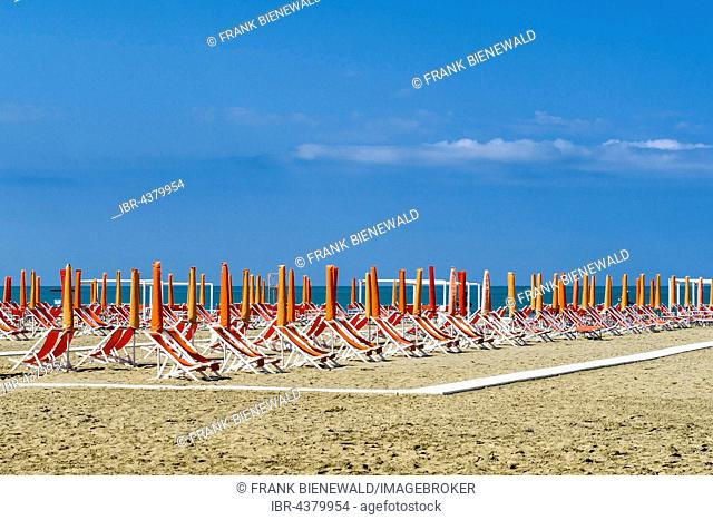 Empty orange deckchairs and sunshades on beach, early season, Viareggio, Tuscany, Italy