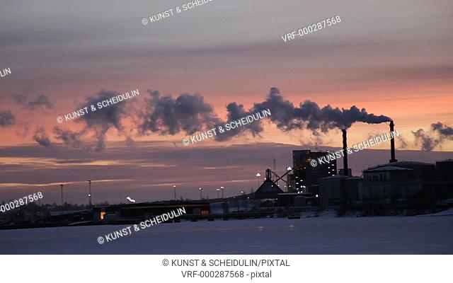 At a frozen bay of the Baltic Sea the chimney stacks of a refinery are fuming at sunset. Örnsköldsvik, Västernorrlands Län, Sweden
