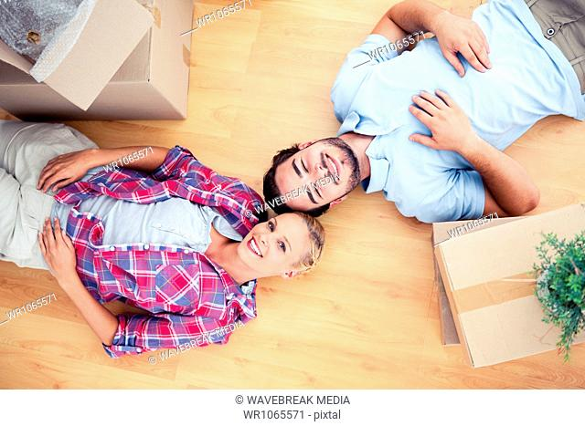 Happy couple lying on the wooden floor