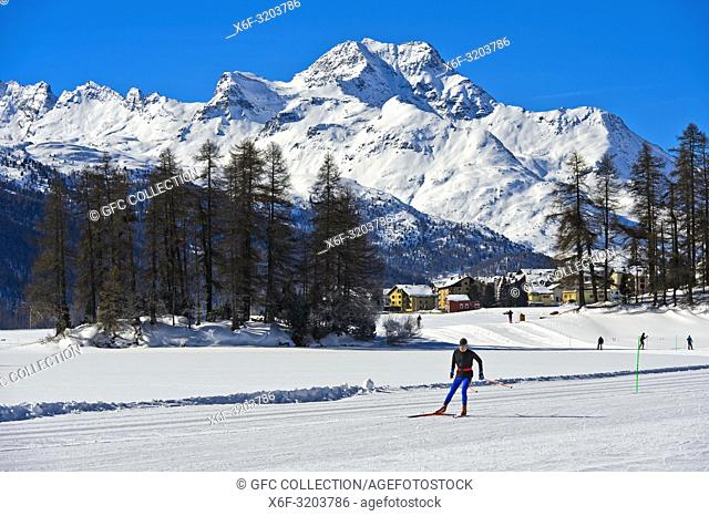 Cross-country skier skiing on the frozen lake Champfersee, peak Gipfel Piz de la Margna behind, Champfer, Engadin valley, Grisons, Switzerland