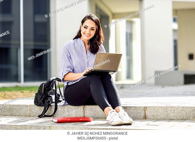 Portrait of smiling student sitting on stair outdoors working on laptop