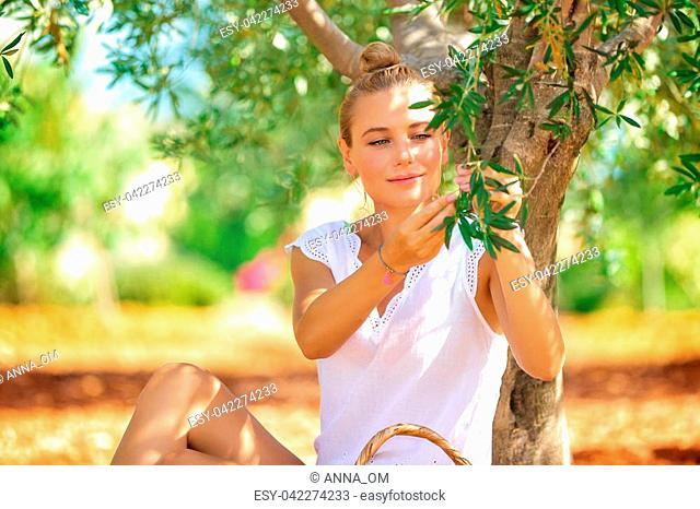 Nice blond woman sitting in the garden near olive tree and picking little green berries, enjoying life in a countryside, fall harvest season