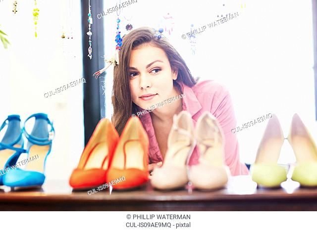 Young woman looking at selection of high heeled shoes