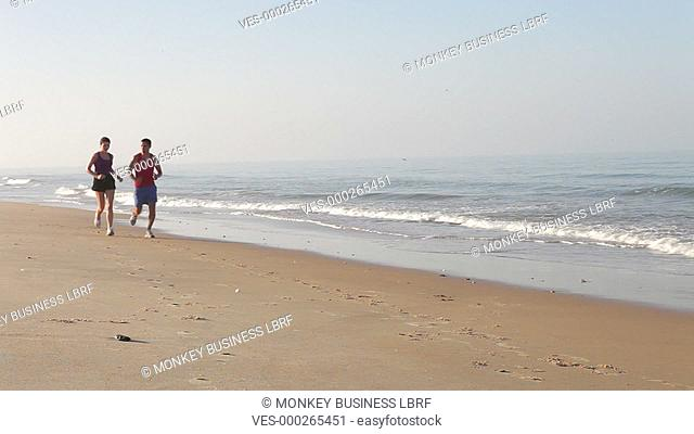 Couple in sportswear running along empty beach towards and then past camera position. Shot on Canon 5d Mk2 with a frame rate of 30fps