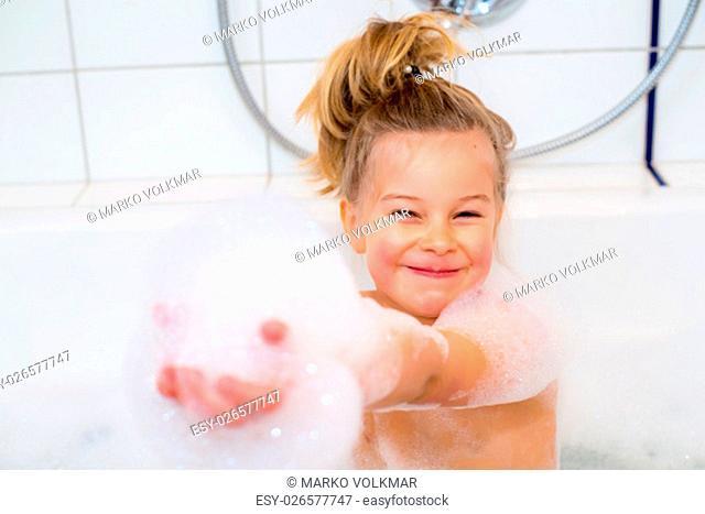 little funny girl with foam bathtub in the bathtub