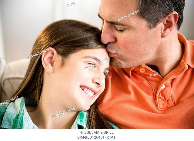 Caucasian father kissing daughter's forehead