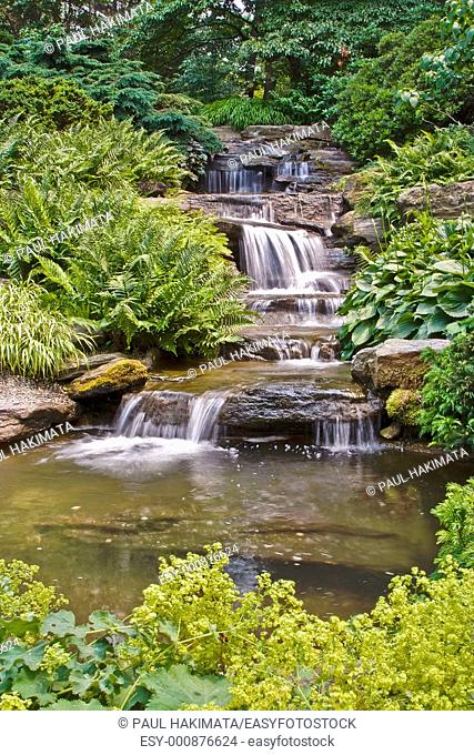 Beautiful multi-layered waterfall between vegetation at the New York Botanical Garden in the Bronx, New York