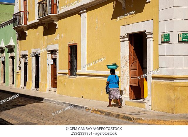 Indigenous woman walking in the street at the historic center of Campeche, Campeche, Yucatan, Mexico, Central America