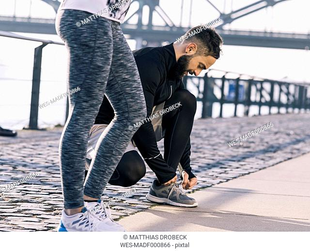 Germany, Cologne, Young couple, workout, man tying shoes