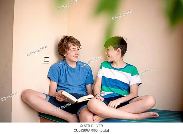 Boys sitting on bed, with book