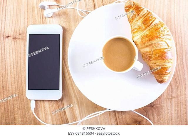 Topview of wooden desktop with blank smartphone, coffee and croissant. Mock up