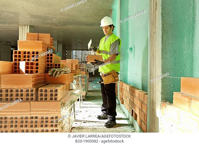 Bricklayer with trowel making a brick wall, Mason with personal protective equipment, PPE, Apartment Building under construction, Donostia, San Sebastian
