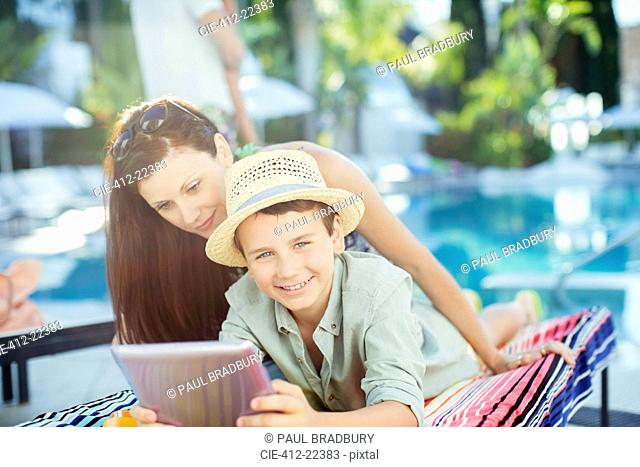 Mother and son using tablet pc by swimming pool