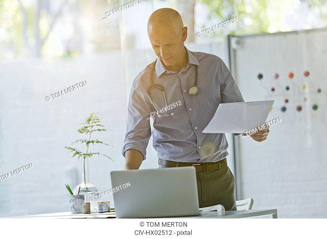 Male doctor with paperwork standing at laptop in doctor's office