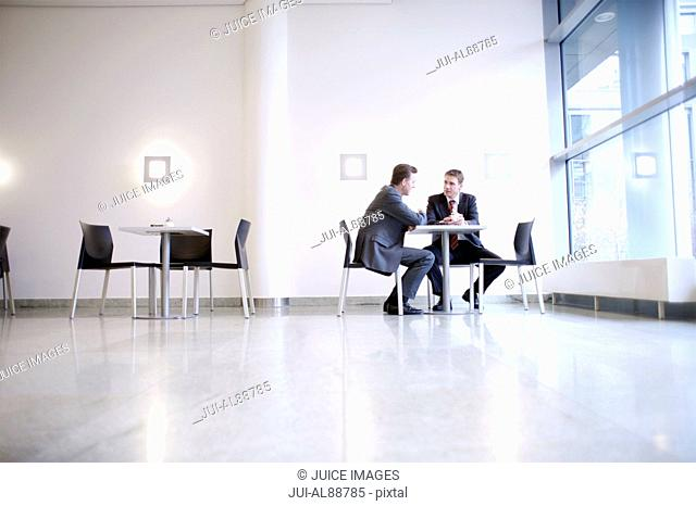 Businessmen talking in cafeteria
