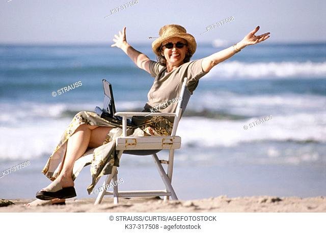 Woman on beach using her laptop computer
