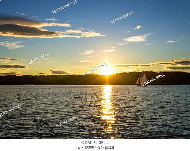 Tranquil seascape with sailboat at sunrise