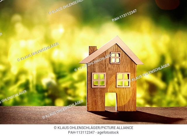 Wooden house on stone floor in front of nature background with bokeh | usage worldwide