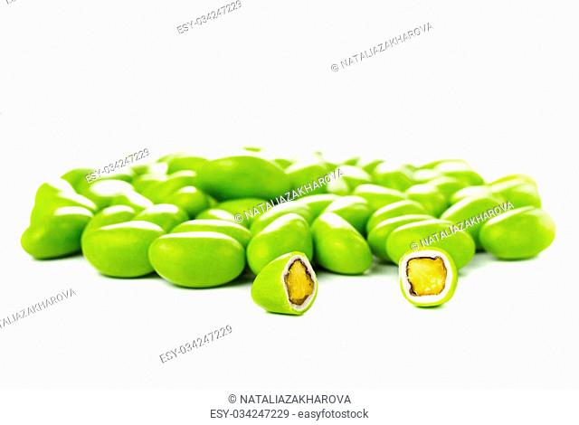 A pile of green gumballs with nuts isolated on a white background