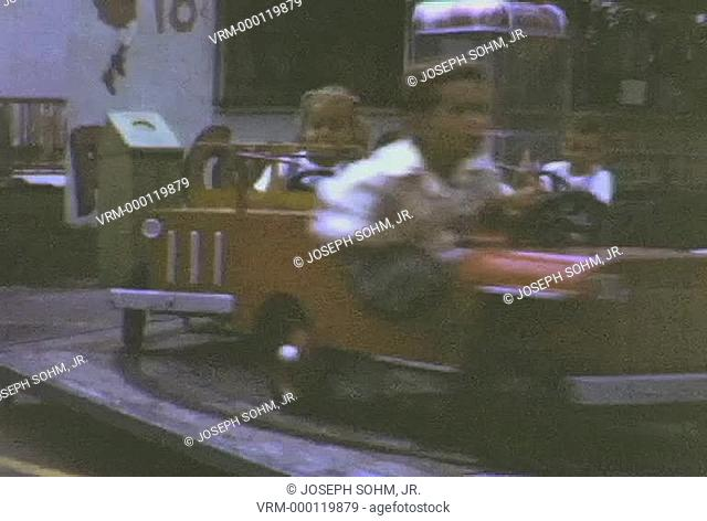 Kids going in circle in little cars and boat on circus ride