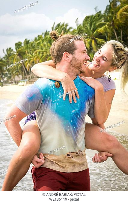 Young couple, man and woman in love, performing piggyback ride at a beach, Riviera Nayarit, Pacific Coast, Mexico