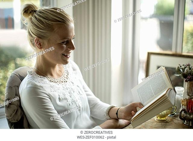 Smiling young woman reading a book at the window
