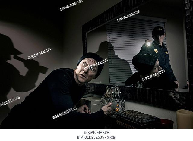 Caucasian police officer shining flashlight on house burglar