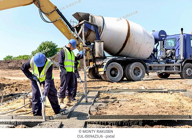 Apprentice builders laying concrete foundations on building site