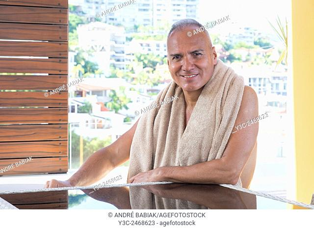 Man, 55 years old, hispanic ethnicity, wearing a towel aroud his shoulders after a bath in swimming pool. Mexico