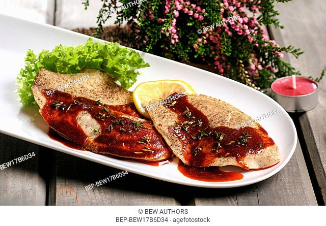 Plaice with red sauce on white plate