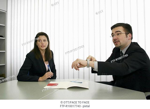Businessman sitting besides businesswoman, showing wristwatch