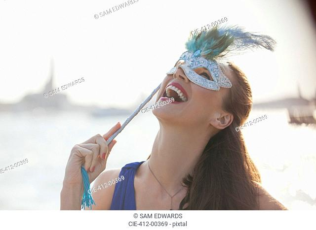 Laughing woman with mask at waterfront in Venice