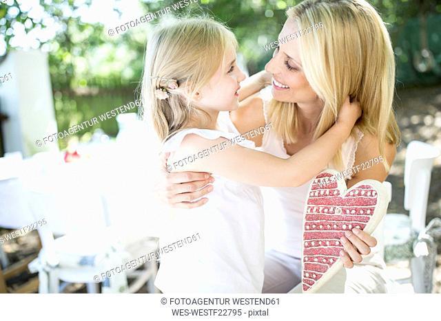 Happy mother receiving heart form her daughter