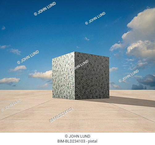 Cube of dollars on concrete