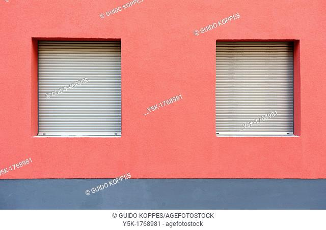 East-Berlin, Germany. Red painted facade of Eastern-German 'Plattenbau' with two closed windows