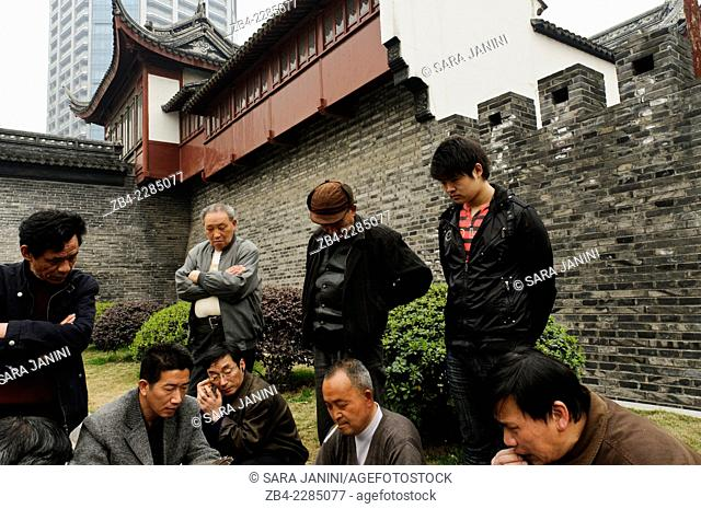 A group of men playing cards outside a temple in Qinglian street, old district, Shanghai, China, Asia