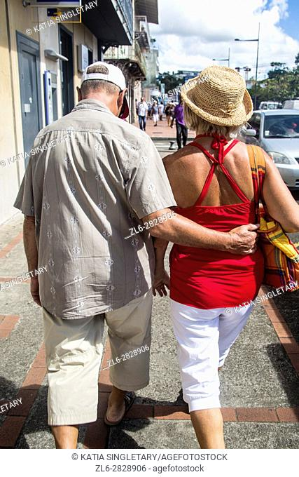 Older mature couple holding each other back, being in love, while strolling the streets of Fort De France