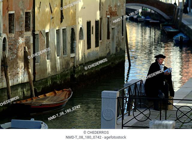Side profile of a person reading a book, Venice, Veneto, Italy