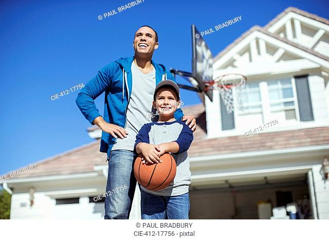 Father and son with basketball in driveway
