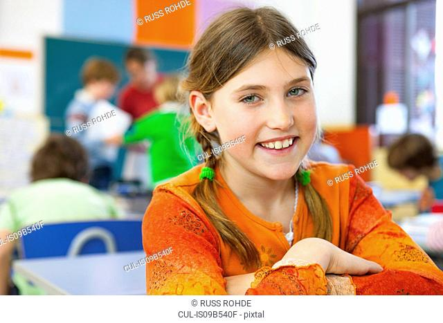 Portrait of primary schoolgirl with plaited hair in classroom