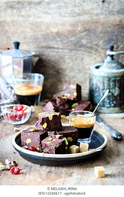 Chocolate fudge with pistachios, sprinkled with cherries, and served with coffee