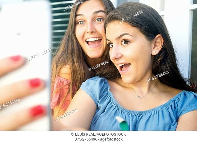 Two happy teenagers laughing and getting a selfie with their mobile phone